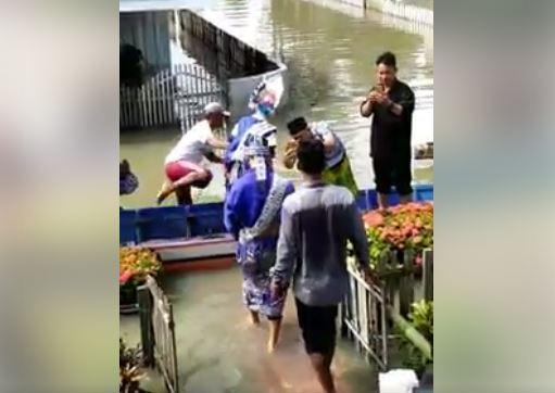 https: img-z.okeinfo.net content 2018 07 06 340 1918765 viral-video-sepasang-pengantin-diangkut-perahu-karena-kampung-dikepung-banjir-SjTft7JuCq.JPG