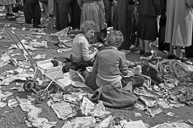Dua perempuan menikmati suasana piknik di antara potongan koran di jalanan, 6 May 1960, ketika putri Margaret menikah dengan fotografer Antony Armstrong-Jones. (Foto: John Turner, sumber dari BBC Indonesia)