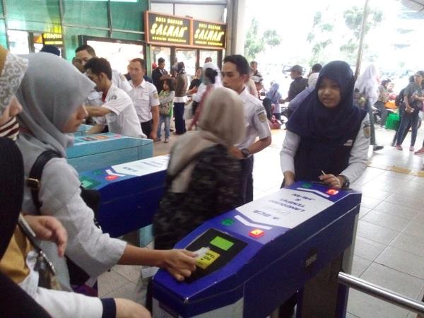 Petugas membantu penumpang men-tap tiket elektronik di Stasiun Depok Baru. (Foto: Febby Novelius/Okezone)