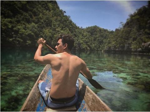 bertelanjang dada Darius terlihat mendayung perahu kayak di sungai yang airnya begitu jernih berkilauan bak kristal.