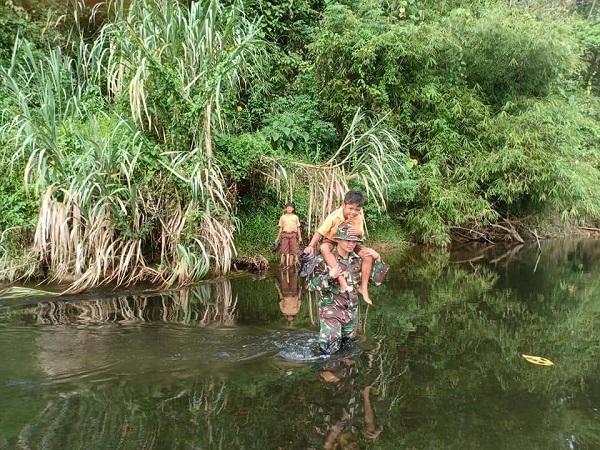 Praka Nanang seberangi sungai Dusun Klawik untuk menuju SDN 04 Bakul bersama anak didiknya. (Foto : Ade Putra/Okezone)