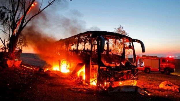 Sebuah bus kosong terbakar setelah terkena roket dari Jalur Gaza. (Getty Images)