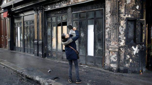 Seorang warga mengabadikan suasana ketika toko-toko dan restoran-restoran di dekat lokasi protes di Paris memilih tutup. (Reuters)