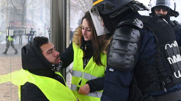 Seorang polisi dan pengunjuk rasa menolong peserta demonstrasi setelah terkena semprotan gas air mata, Sabtu (1/12/2018). (Alain Jocard/Getty Images)
