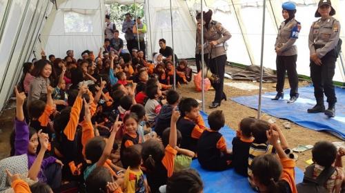 Polwan hibur anak-anak korban gempa untuk hilangkan trauma akibat bencana alam itu di Posko Pengungsian Desa Tanjung, Lombok Utara, NTB, Rabu (8/8/2018). (Foto: Puteranegara Batubara/Okezone)