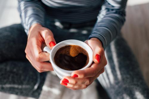 Perempuan memegang cangkir kopi