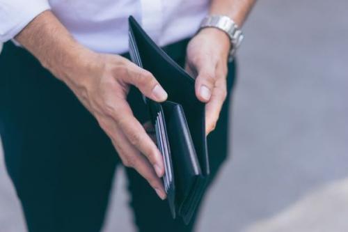 Pria memegang dompet