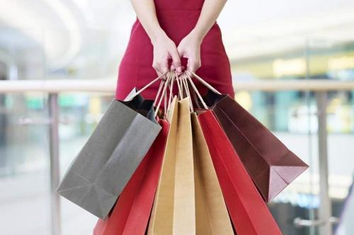Perempuan memegang kantung belanja