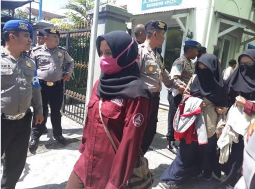 Para Peserta Peluncuran Buku Haqiqatul Wahy Keluar Lokasi Acara dengan Pengawalan Polisi (foto: Julia Alazka untuk BBC News Indonesia)