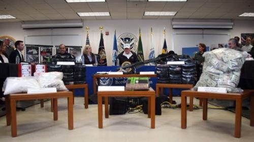 Trump memberikan keterangan di antara tumpukan senjata, uang, dan obat-obatan terlarang yang disita oleh patroli petugas perbatasan AS (AFP)
