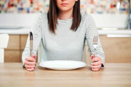Perempuan memegang sendok dan garpu