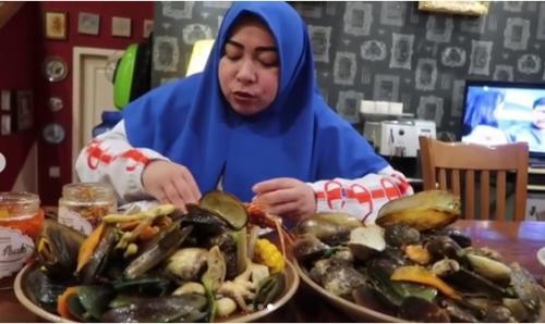 wanita berusia 45 tahun ini tetap menyantap dengan lahap seafood yang ada di depannya