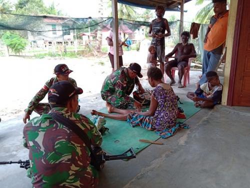 Personel Yonif Mekanis (Yonmek) 521/DY memberikan pelayanan kesehatan kepada masyarakat di perbatasan RI-Papua Nugini. (Dispenad)