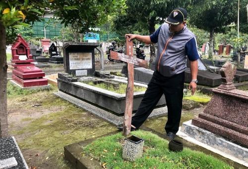 Pengurus makam saat hendak memasang kembali kayu penanda yang sudah sedikit terbakar di Makam Bethesda. (Foto Harminanto krjogja)
