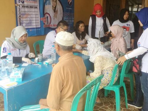 Caleg DPRD Tangsel dari Partai Perindo, Renny Suryani (kerudung merah), saat memberi pelayanan kesehatan gratis bagi masyarakat. (Foto : Hambali/Okezone)