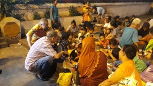 Dewan pembina wihara dan tokoh Tionghoa Muslim Indonesia, Yusuf Hamka, bercengkerama dengan warga yang berbuka puasa. (BBC Indonesia)