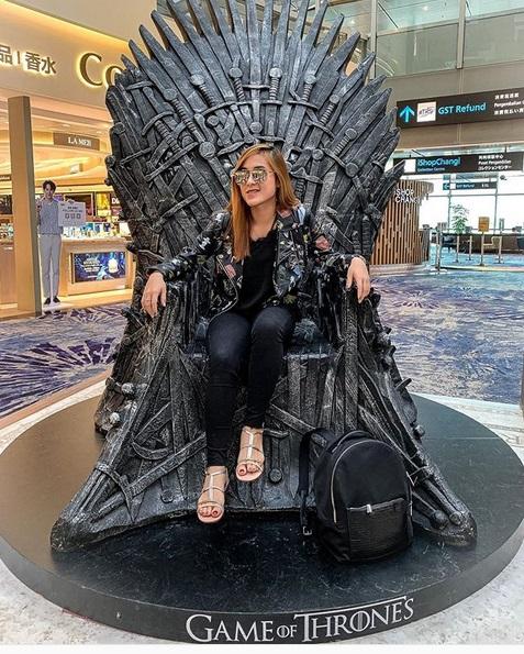 Perempuan duduk di kursi Game of Thrones