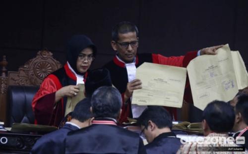 Hakim MK Saldi Isra memegang kertas