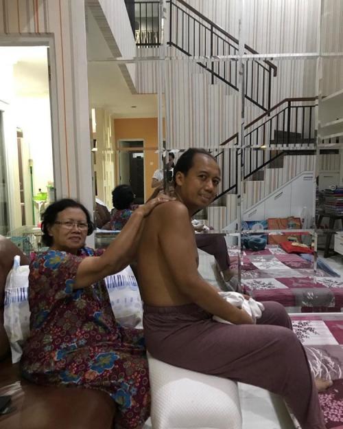 Sri Roosmandari sedang memijat anaknya, Sutopo