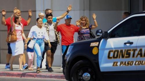 Para pelanggan yang syok keluar gedung sambil mengangkat tangan. (Reuters)