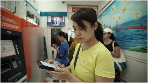 PMI di Hong Kong sedang Melakukan Transaksi dengan Mobile Banking BNI. Layanan digital BNI Sudah Bisa Dinikmati oleh Pekerja Migran Indonesia di Hong Kong.