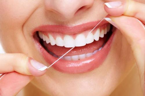 Perempuan memakai dental floss