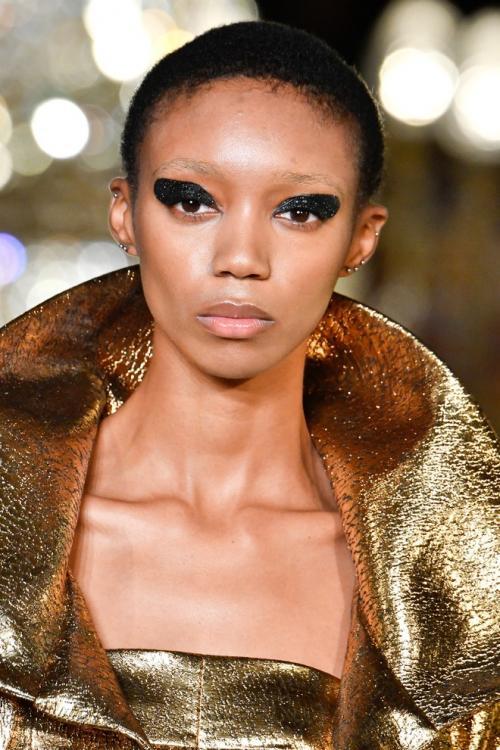 Diaplikasikan mulai dari garis kelopak mata sampai ke pelipis, ditambah eyeliner hitam, baru disempurnakan dengan pulasan coat glitter.