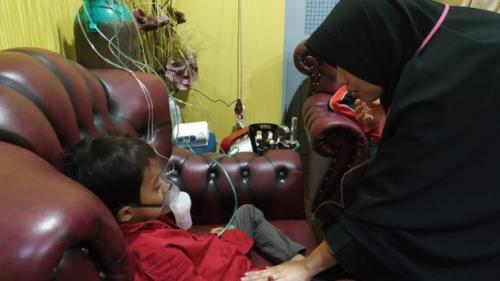 Warga Pekanbaru Ernawati merawat salah satu anaknya, Ababil (6), yang batuk-batuk dan kesulitan bernapas akibat karhutla. (Foto: BBC News Indonesia)