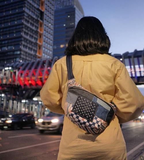 Perempuan berdiri pakai tas
