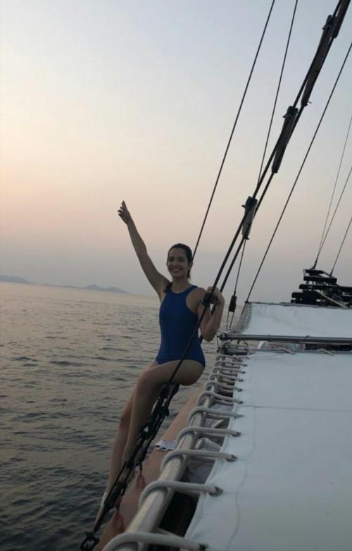 Mumpung di pantai, hot mama ini pakai bikini warna biru terang, gayanya foto manja di pinggir kapal phinisi.