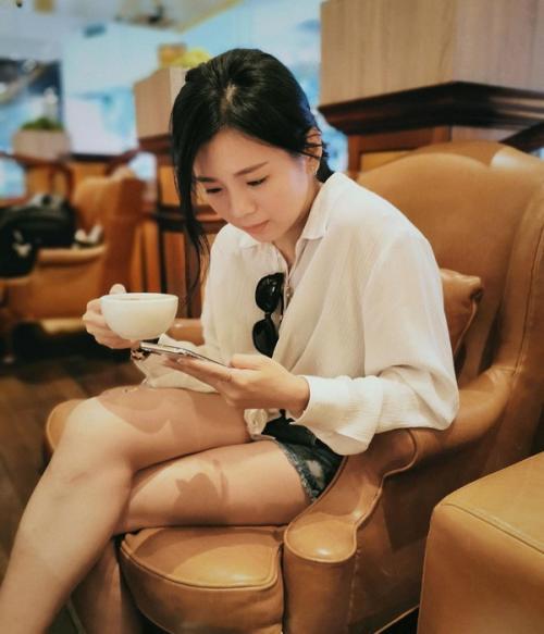 Dengan balutan kemeja putih lengan panjang oversize, dan hotpants jeans dengan motif sobek, Goh duduk di sofa cokelat