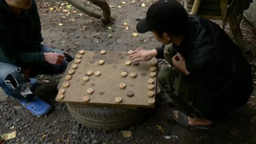 Para migran bermain sambil minum teh. (BBC)