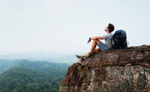 Pria duduk di tebing