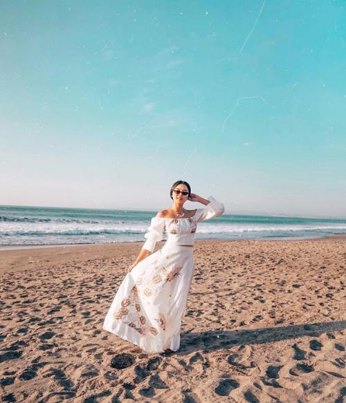 di foto ini Maria tampak berada di pinggir pantai dan berdiri telanjang kaki di atas pasir