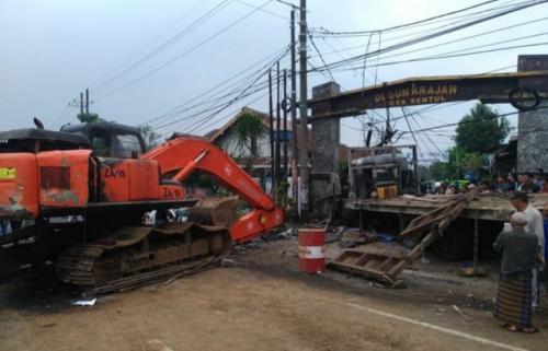 Alat berat yang dibawa truk tronton terguling di Pasuruan. (Foto: Ist)