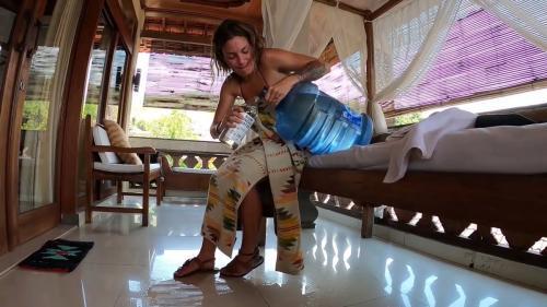 Perempuan memegang galon air