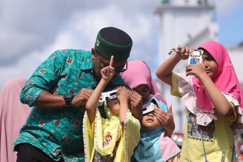 Warga menyaksikan gerhana matahari cincin di halaman Masjid Baiturrahmah, Simeulue, Aceh, Kamis (26/12/2019). (Foto : Okezone.com/Windy Phagta)