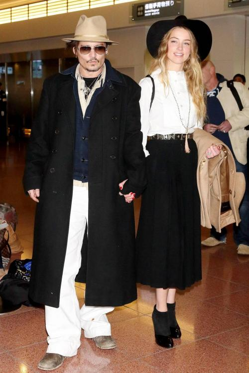 Amber mengenakan paduan blus putih dan rok hitam, serta topi hitam berukuran besar.