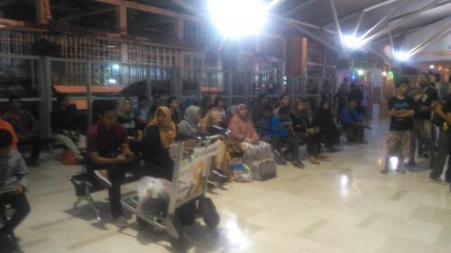 Keluarga menunggu kedatangan kerabatnya yang telah diobservasi di Natuna di Bandara Sultan Hasanuddin (Foto : Okezone.com/Herman Amiruddin)