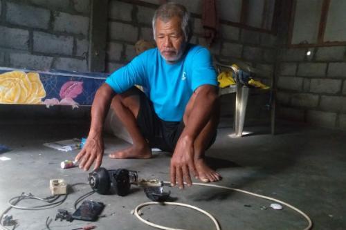 Zamhari, kakek korban menunjukan gawai dan headset milik cucu yang rusak tersambar petir. (Harian Jogja/Ujang Hasanudin)