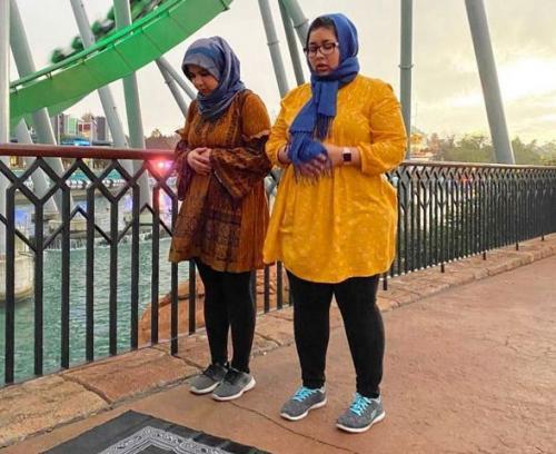 Muslimah sholat di bawah roller coaster. (Foto: Instagram @placesyoullpray)