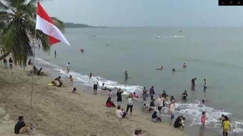 Wisatawan tak kenakan masker saat main di pantai di kawasan Pandeglang Banten (iNews/Iskandar Nasution)