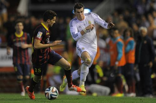 Gareth Bale berlari keluar lapangan demi melewati Marc Bartra (Foto: Goal)