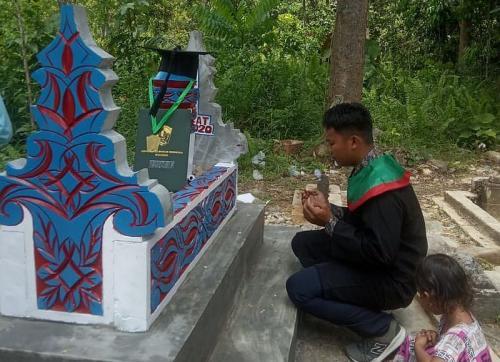 Momen haru wisudawan menyematkan topis wisuda di makam ayahnya (Foto : Okezone.cpm/Herman)