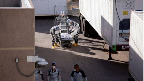 Para tahanan memindahkan jenazah pasien Covid.(Reuters)