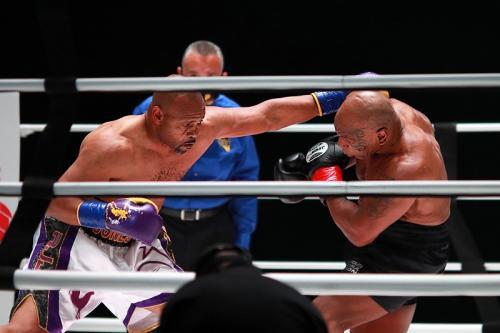 Roy Jones Jr layangkan pukulan ke arah Mike Tyson (Foto: Reuters/Joe Scarnici)