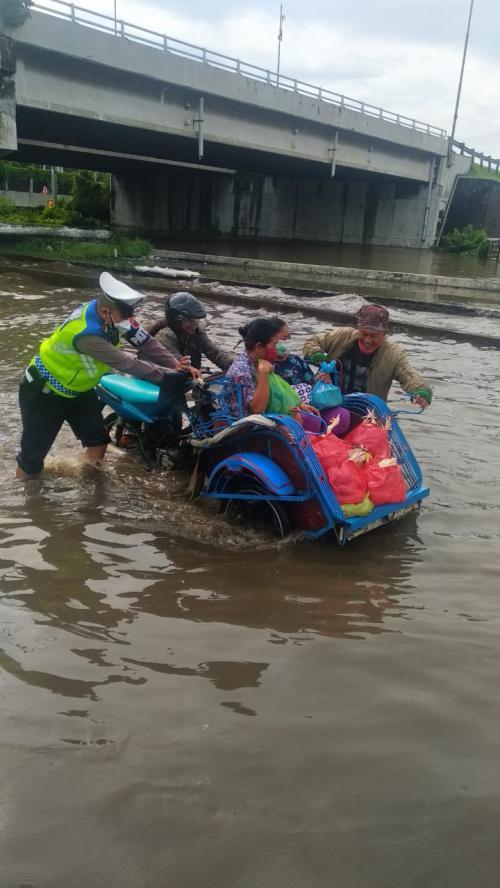 Polisi bantu tukang becak menerobos banjir Semarang (Foto : Istimewa)
