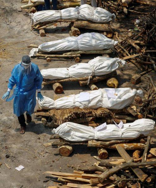 Seorang tenaga kesehatan berjalan melewati tumpukan kayu kremasi. (Adnan Abidi/Reuters)