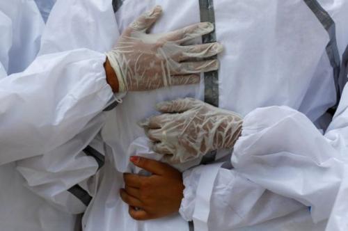 Orang-orang saling menguatkan selama proses pemakaman dengan cara kremasi. (Adnan Abidi/Reuters)